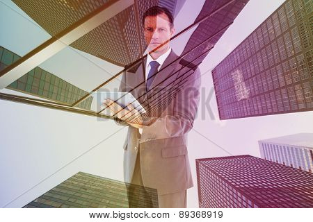 Serious charismatic businessman holding a tablet computer against skyscraper