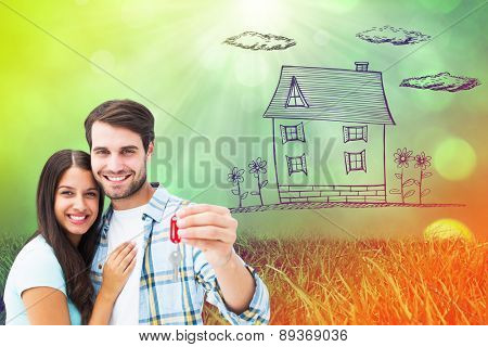 Happy young couple holding new house key against field against glowing lights