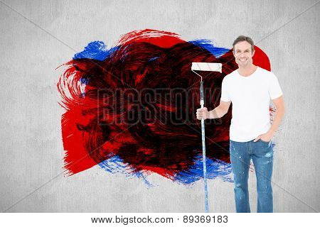 Confident man holding paint roller on white background against white and grey background