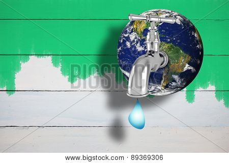 Earth with faucet against green paint on fence
