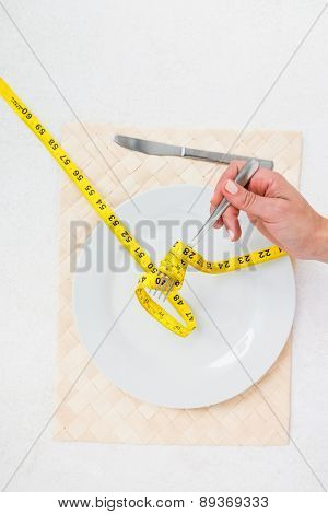 Measuring tape around the fork on white background