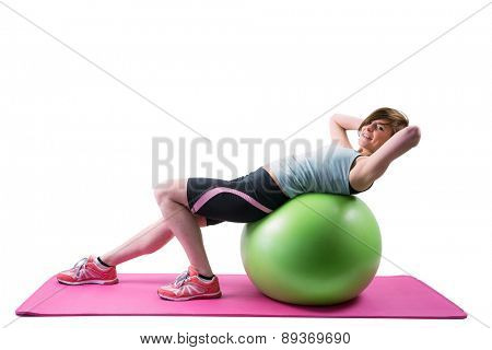 Pretty brunette looking at camera and exercising on fitness ball on white background