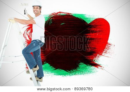 Portrait of man on ladder painting with roller against green red and black paint