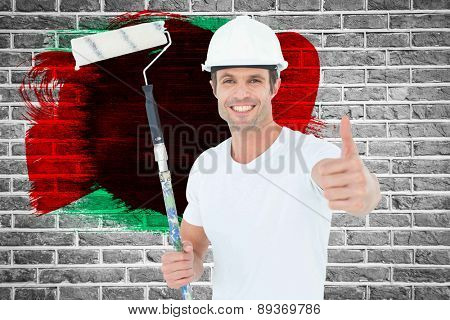 Man holding paint roller while gesturing thumbs up against red brick wall