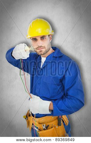 Confident repairman holding cables against white background