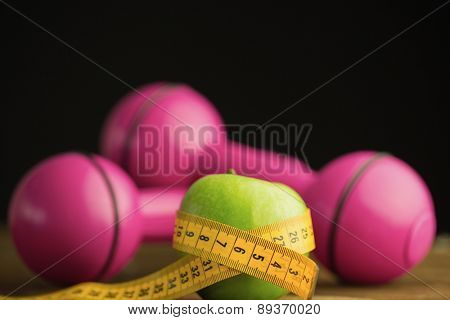 Pink dumbbells with green apple and measuring tape on wooden background