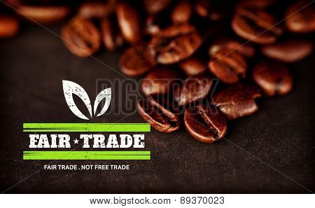 fair trade stamp against dark blurred coffee seeds laid out together on a black table