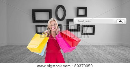 Stylish blonde in red dress holding shopping bags against big room with several frames at wall