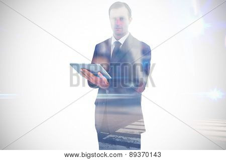 Serious charismatic businessman holding a tablet computer against blurred new york street