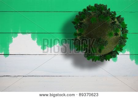 Sphere covered with forest against green paint on fence