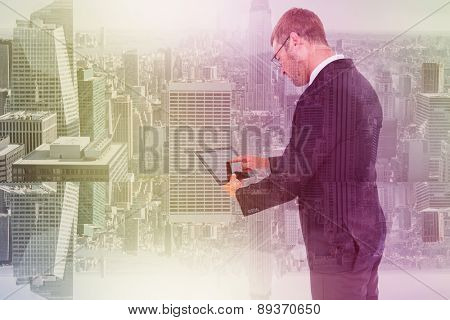 Businessman using his tablet pc against room with large window looking on city