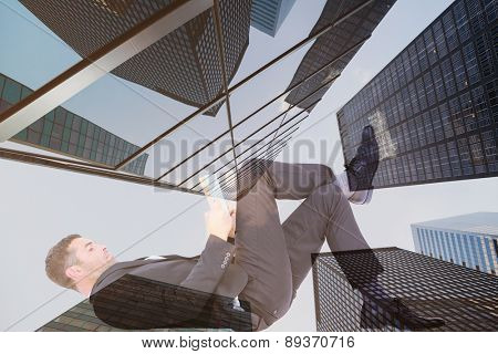Businessman lying on the floor reading book against skyscraper