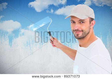 Handyman holding paint roller against blue sky