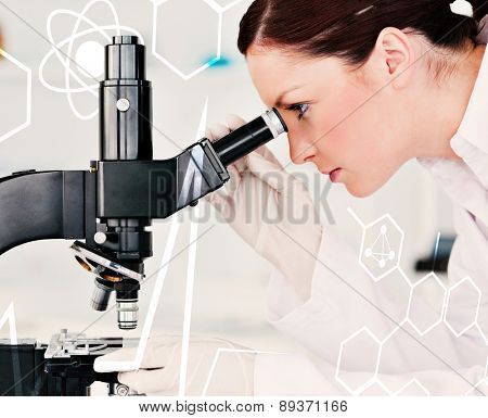Attractive redhaired scientist looking through a microscope against science and medical graphic