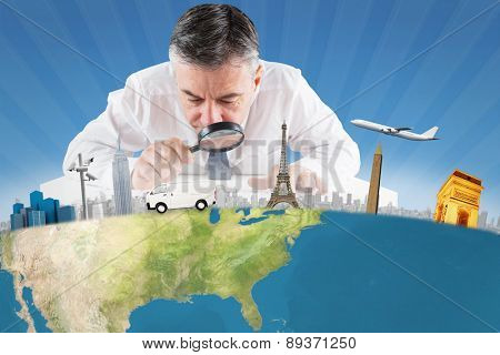 Mature businessman examining with magnifying glass against cool linear pattern in blue