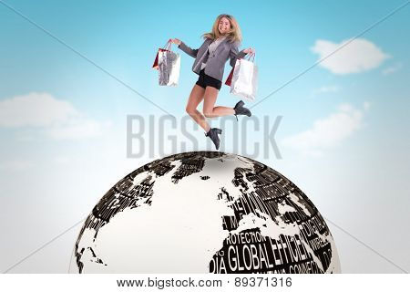 Stylish blonde jumping with shopping bags against blue sky