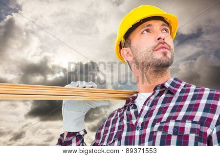 Handyman holding wood planks against blue sky with white clouds