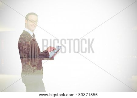 Happy businessman using his tablet pc against room with large window looking on city