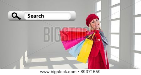 Blonde in winter clothes holding shopping bags against white room with windows