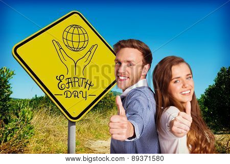 Happy young couple gesturing thumbs up against mountain trail