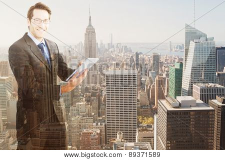 Businessman looking at the camera while using his tablet against new york