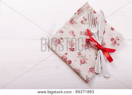 Cutlery, tablecloth on white wooden table for dinner.