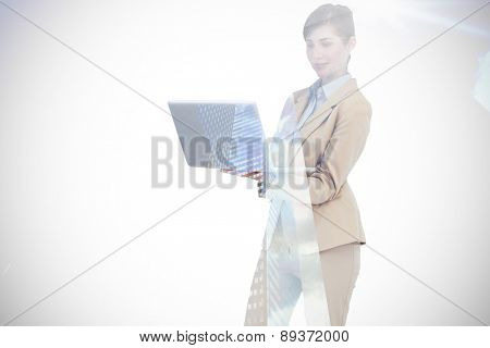 Confident businesswoman holding laptop against low angle view of skyscrapers