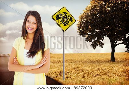 Happy casual woman smiling at camera against road leading out to the horizon