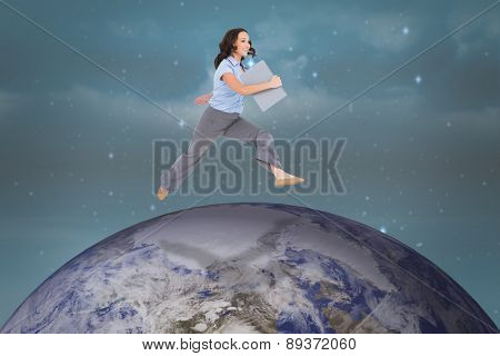Cheerful classy businesswoman jumping while holding clipboard against stars twinkling in night sky