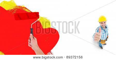 Handyman holding paint roller against red and yellow paint
