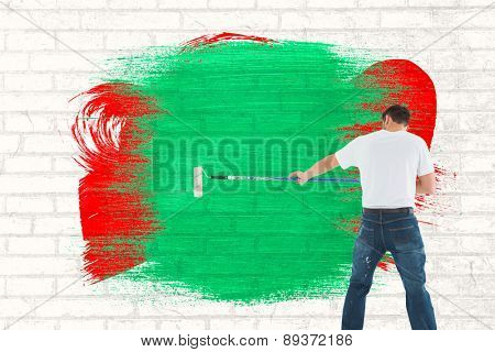 Man using paint roller on white background against white wall
