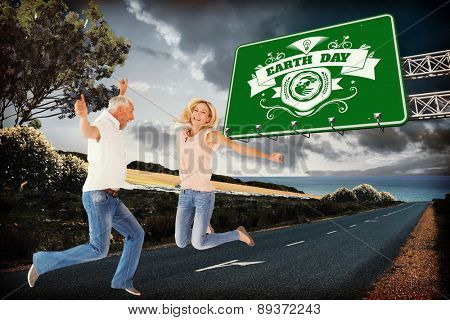 Excited couple cheering and jumping against scenic backdrop