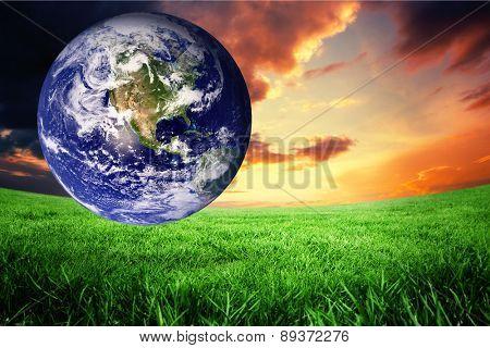 earth against green field under orange sky