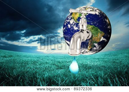 Earth with faucet against blue sky over green field