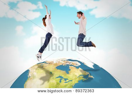Couple jumping in the air against blue sky