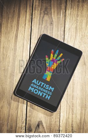 Autism awareness month against overhead of tablet on desk