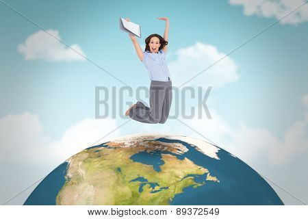 Happy classy businesswoman jumping while holding clipboard against blue sky