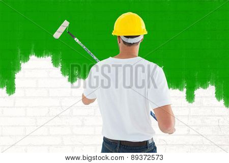 Man using paint roller against white wall
