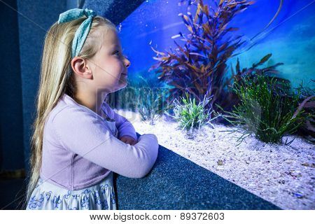Happy young woman looking at fish in tank at the aquarium