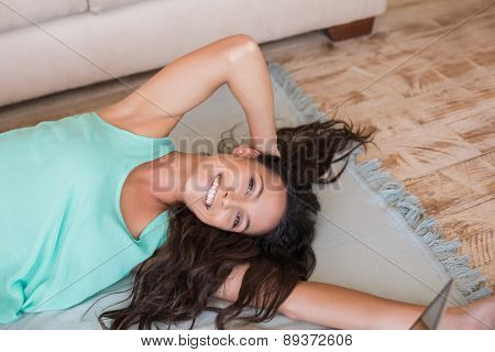Pretty brunette lying on the floor at home in the living room