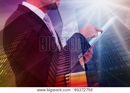 Businessman using his tablet pc against low angle view of skyscrapers at sunset