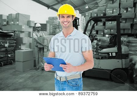 Happy architect holding clip board against warehouse worker loading up pallet