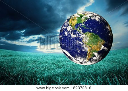 earth against blue sky over green field