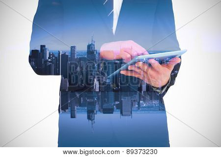 Businessman touching his tablet pc against mirror image of city skyline