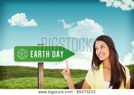 Happy casual woman pointing up against road leading out to the horizon