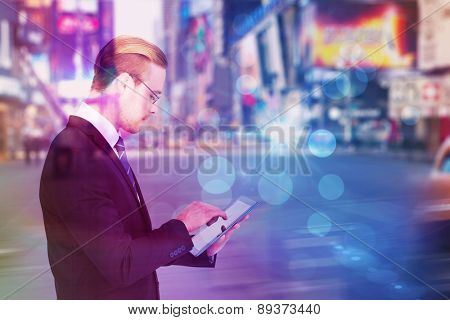 Businessman in reading glasses using his tablet pc against blurry new york street