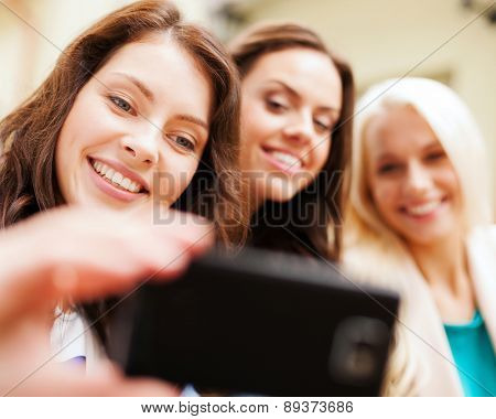 holidays and tourism concept - beautiful girls taking selfie in the city