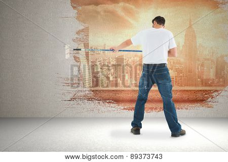 Man using paint roller on white background against sun shining over city