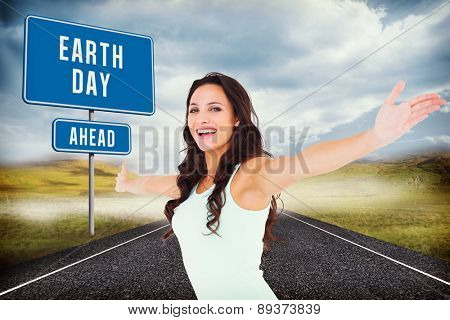Carefree brunette with arms out against cloudy landscape background with street