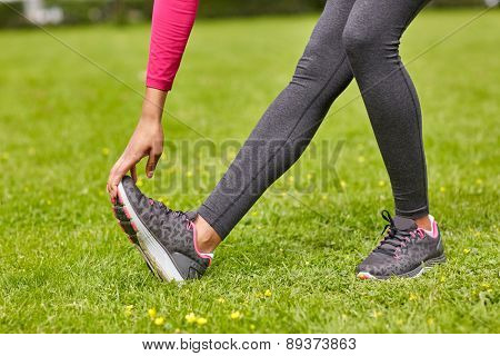 fitness, sport, training, people and lifestyle concept - close up of woman stretching leg in park